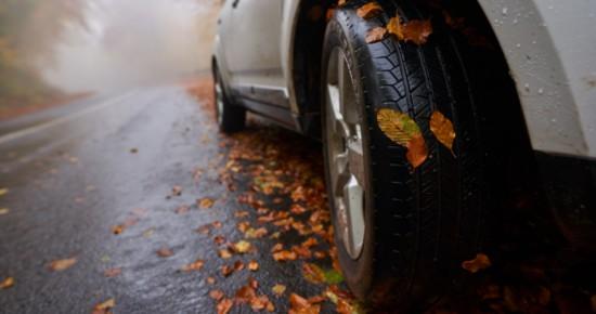 Pneu hiver sur route glissante en automne, avec des feuilles mortes
